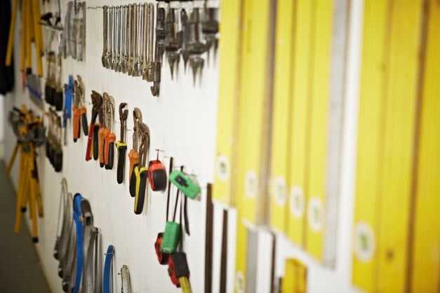Essential tools for a gas engineer blog image shows a selection of tools hanging from the wall - spirit levels, tape measures, pliers.
